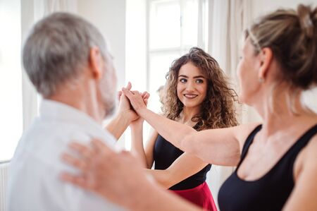Photo for Senior couple in dancing class with dance teacher. - Royalty Free Image