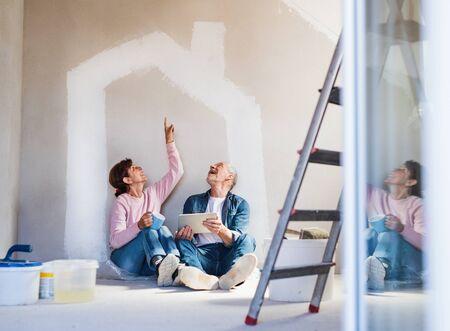 Photo pour Senior couple painting walls in new home, using tablet. Relocation concept. - image libre de droit