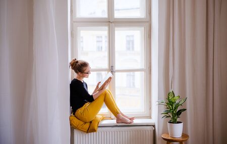 Photo pour A young female student with a book sitting on window sill, studying. - image libre de droit