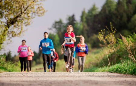Foto de Large group of multi generation people running a race competition in nature. - Imagen libre de derechos