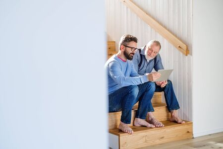 Photo for An adult son and senior father with tablet sitting on stairs indoors at home. - Royalty Free Image
