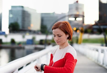 Foto de Young woman with smartwatch on bridge outdoors in city, resting after exercise. - Imagen libre de derechos