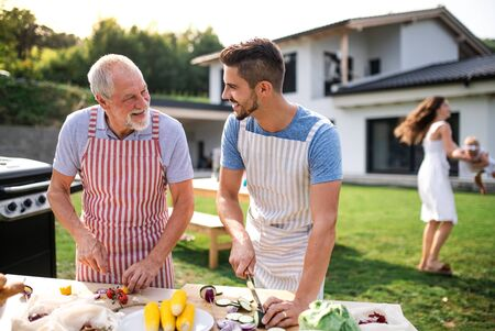 Photo pour Portrait of father and son outdoors on garden barbecue, grilling. - image libre de droit