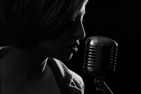 Photo for Silhouette of singing woman with retro microphone - Royalty Free Image