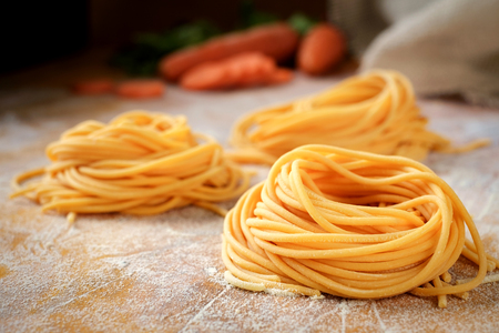 Foto de Fresh spaghetti sockets with carrots on the wooden table. Traditional Italian raw pasta - Imagen libre de derechos
