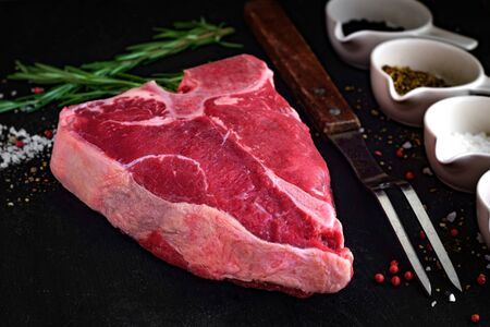 Foto de a big raw porterhouse steak with spices lying on a dark wooden table - Imagen libre de derechos