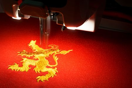 Foto de The embroidery machine embrodering gold lion design on red fabric, close up picture, copy space on the right - Imagen libre de derechos