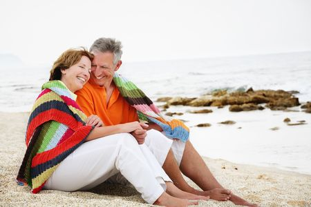 Foto de Happy mature couple sitting on the beach.  - Imagen libre de derechos