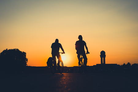 Foto de silhouette of a person riding bicycle with sunset sky background - Imagen libre de derechos