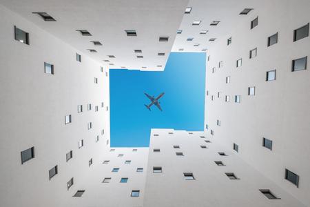 Foto de airplane in sky above building court - plane over courtyard - Imagen libre de derechos
