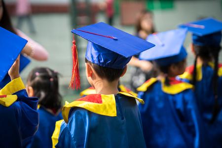 Photo pour Diploma graduating little student kid outdoor closeup - image libre de droit