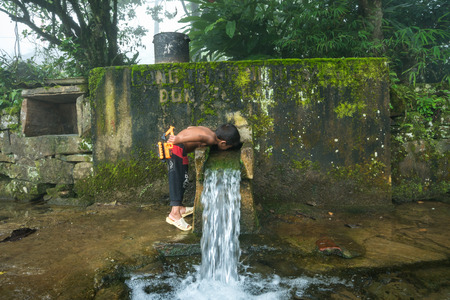 Photo pour Lao Cai, Vietnam - Sep 7, 2017: Ethnic minority child drink water from small spring downstream from mountain in Y Ty, Bat Xat district - image libre de droit