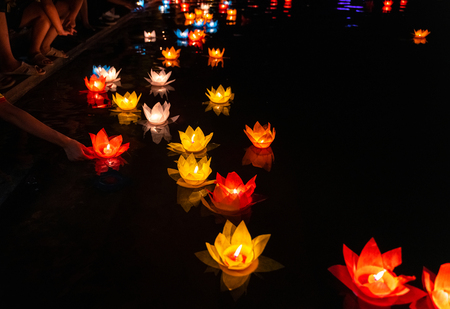 Foto de Floating colored lanterns and garlands on river at night on Vesak day for celebrating Buddha's birthday in Eastern culture, that made from paper and candle - Imagen libre de derechos