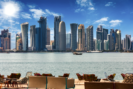 Photo for The skyline of Doha, Qatar with chairs and tables in front - Royalty Free Image