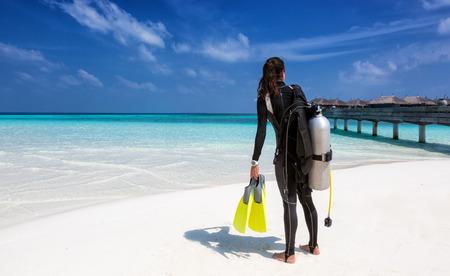 Photo pour Female scuba diver with diving equipment on the beach at the Maldives - image libre de droit