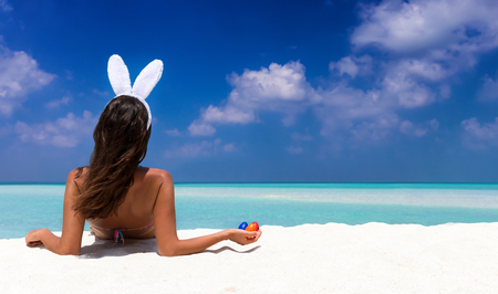 Photo for Woman with bunny ears and colorful easter eggs on a tropical beach in the Maldives - Royalty Free Image