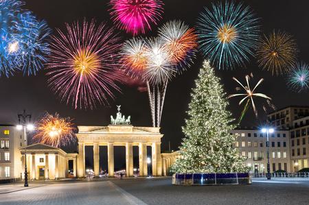Foto de Brandenburg Gate in Berlin, Germany, with fireworks and Christmas tree - Imagen libre de derechos