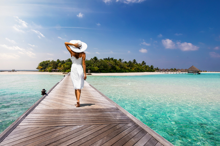 Photo for Attractive woman in white walks over a wooden jetty towards a tropical island - Royalty Free Image