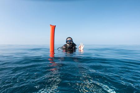 Foto de Female scuba diver with surface marker buoy showing the OK sign - Imagen libre de derechos
