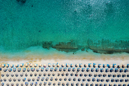 Foto de Aerial topdown view to the beach of Kalafatis with symmetrical lined up umbrellas and sunbeds, Mykonos, Cyclades, Greece - Imagen libre de derechos