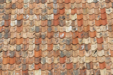 Photo pour Roof made of aged roofing tiles in different shades of orange. The newly  replaced tiles are darker and the older is covered with lichen - image libre de droit
