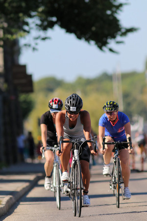 STOCKHOLM - AUG 23, 2015: Cycling young woman wearing sun-glasses followed by two de-focused competitors at ITU World Triathlon event in Stockholm, 2015