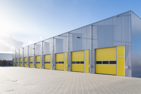 Photo for exterior of a commercial warehouse with yellow roller doors - Royalty Free Image