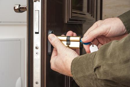 Foto de Locksmith replacing a cylinder lock - Imagen libre de derechos