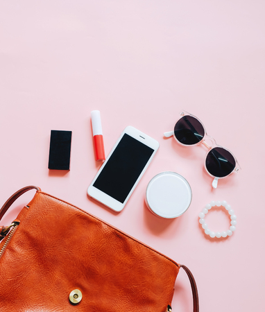 Photo for Flat lay of brown leather woman bag open out with cosmetics, accessories and smartphone on pink background - Royalty Free Image