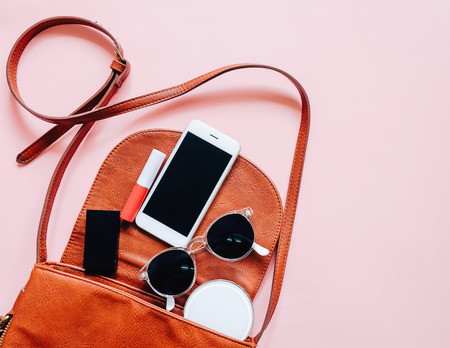 Photo pour Flat lay of brown leather woman bag open out with cosmetics, accessories and smartphone on pink background - image libre de droit