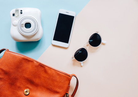 Photo pour Flat lay of brown leather woman bag open out with accessories, instant camera and smartphone on colorful background - image libre de droit