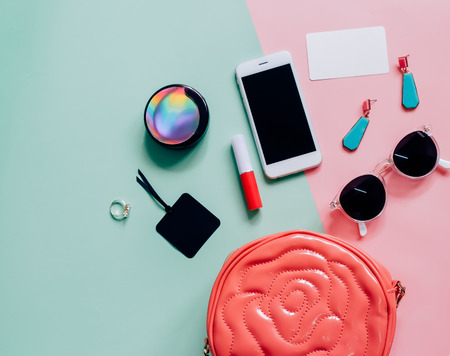Photo for Flat lay of pink cute woman bag open out with cosmetics, accessories, tag card and smartphone on colorful background with copy space - Royalty Free Image