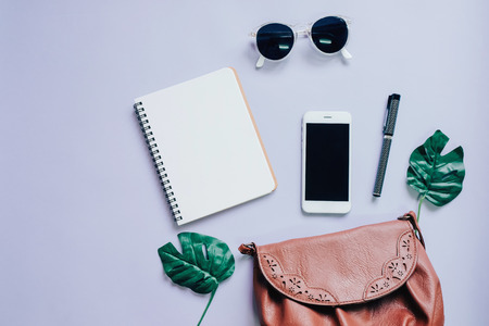 Photo pour Top view flat lay of woman bag with smartphone, blank notebook, sunglasses and green leaf, copy space - image libre de droit
