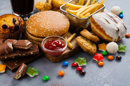 Photo for Assortment of unhealthy products thats bad for figure, skin, heart and teeth. Fast carbohydrates food. Space for text - Royalty Free Image