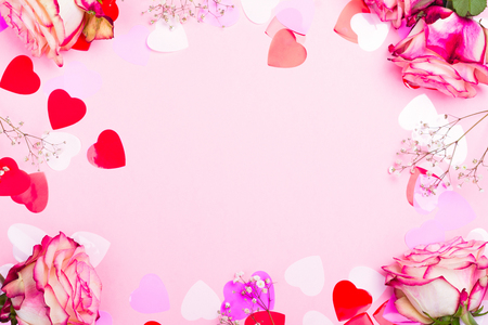 Foto de Beautiful pink rose, decorative confetti hearts and pink ribbon on pink Valentines day background - Imagen libre de derechos