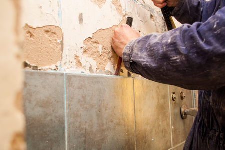 Photo pour Flat renovation, ceramics, master robbing old tiles in the bathroom with a hammer - image libre de droit