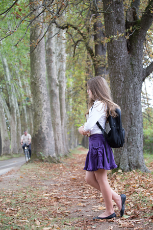 Photo for Pretty little long hair blonde schoolgirl with backpack posing and standing in the alley park holding books back to school in the nature autumn - Royalty Free Image