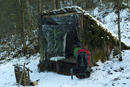 Photo for Improvised, deliberately primitive lean-to shelter from poles, bark and branches in the winter snow-covered forest. In the foreground is a red modern backpack. - Royalty Free Image