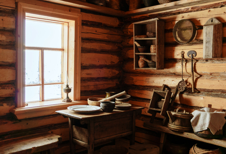 Photo pour fragment of the interior of an old peasant log cabin - a table with wooden and ceramic dishes, a kerosene lamp - image libre de droit