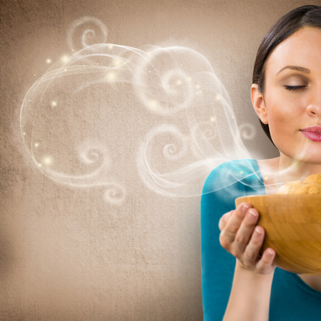 Foto de Beautiful woman holding hot fresh smelling oat cookies with closed eyes and relaxing. Retro stylized enjoying food poster with place for your text on grunge background - Imagen libre de derechos