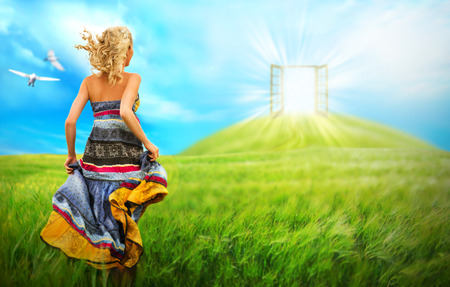 Foto de Young woman running across beautiful field to the bright luminous door on a hill. Bright future affection concept - Imagen libre de derechos