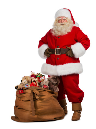 Foto de Full length portrait of a Santa Claus posing near a bag full of gifts isolated on white background - Imagen libre de derechos