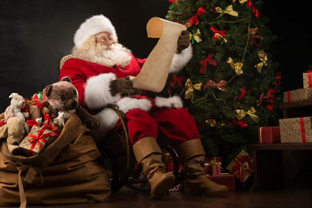 Foto de Portrait of happy Santa Claus sitting at his room at home near Christmas tree and big sack and reading Christmas letter or wish list - Imagen libre de derechos