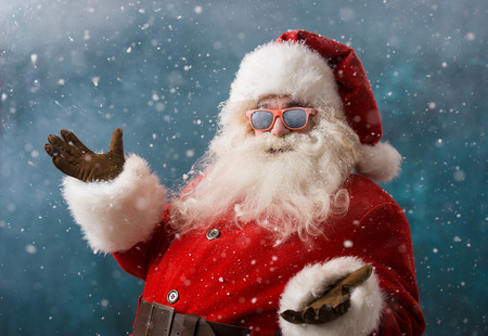 Photo pour Santa Claus wearing sunglasses dancing outdoors at North Pole in snowfall. He is celebrating Christmas after hard work - image libre de droit