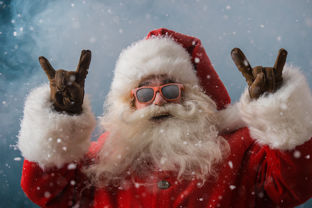 Foto de Santa Claus wearing sunglasses dancing outdoors at North Pole in snowfall. He is celebrating Christmas after hard work - Imagen libre de derechos