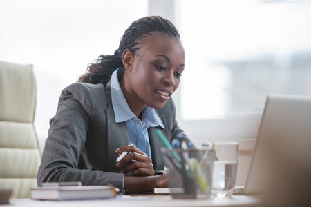 Photo pour Pretty african business woman working on laptop in office - image libre de droit