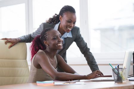 Foto de Young african business women in office working together on laptop - Imagen libre de derechos