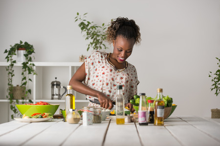 Photo pour Young African Woman Cooking. Healthy Food - Vegetable Salad. Diet. Dieting Concept. Healthy Lifestyle. Cooking At Home. Prepare Food - image libre de droit