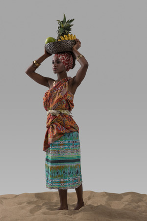 Photo for Attractive young african woman carrying fruits on sand on gray studio background - Royalty Free Image