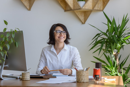 Photo for Woman smiling at office during working day - Royalty Free Image